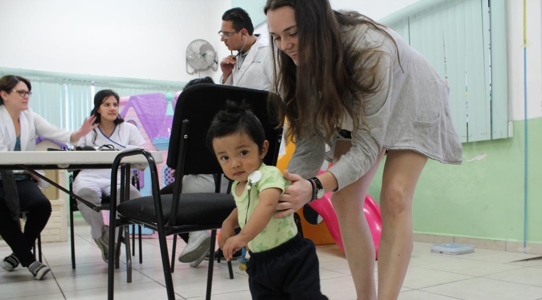 A female intern with Projects Abroad is pictured helping a child learn to walk as part of her physiotherapy internship in Mexico.